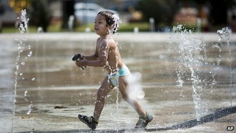 A boy runs through a water fountain in Buenos Aires on 26 December, 2013