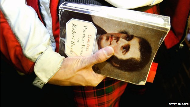 Man with traditional Scottish tartan holds a book with Robert Burns face on it at Burns Night in January