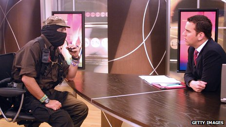 Subcomandante Marcos (left) is interviewed by journalist Carlos Loret de Mola on Televisa on 9 May, 2006