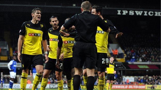 Angry Watford players surround referee Graham Scott