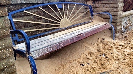 Bench covered in sand of Felixstowe beach front