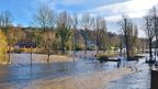 A river has burst its banks and brown water surrounds everything, including a footbridge, lamp posts and trees.