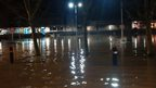 A car park is flooded at night.