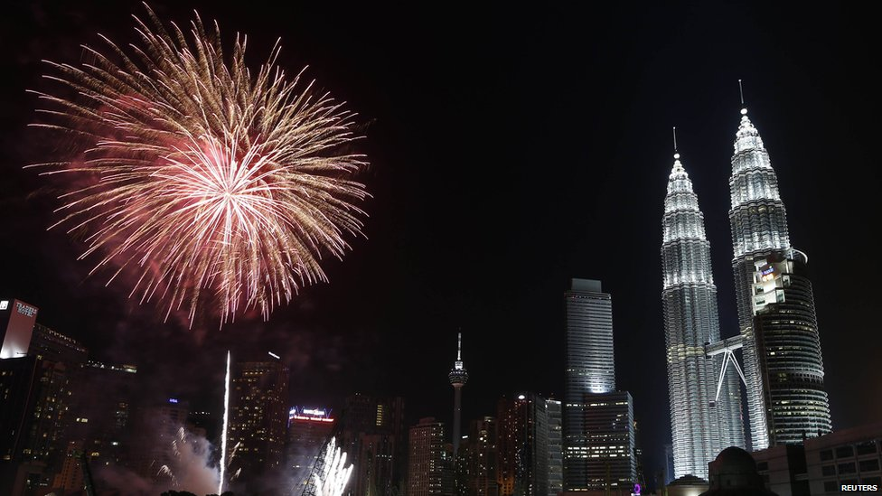 Fireworks explode near Malaysia's landmark Petronas Twin Towers during New Year celebrations in Kuala Lumpur January 1, 2014