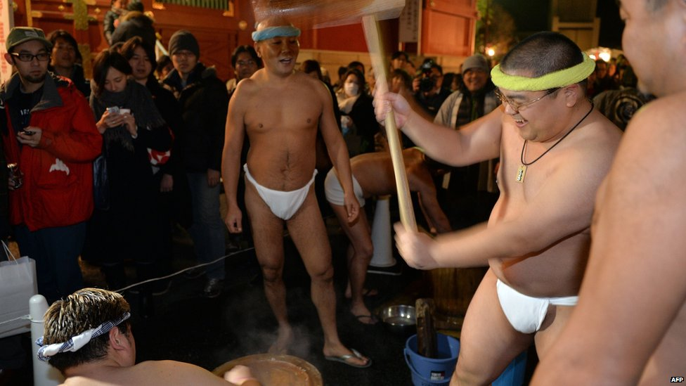 Naked men in loincloths pound steamed rice into a mochi rice cake to celebrate the New Year at the Kanda shrine in Tokyo on January 1, 2014