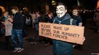 Protesters wearing white-faced Guy Fawkes masks. Photo: Fabian Jansen