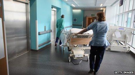 Two medical staff wheel a bed along a hospital corridor