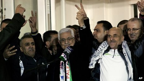 President Mahmoud Abbas holds hands with Palestinian prisoners released on 31 December 2013