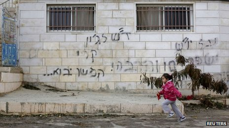 "A girl runs past graffiti on a house in the West Bank village of Dahiyat al-Zira that reads: ""Regards to John Kerry - to be continued"" (31 December 2013)"