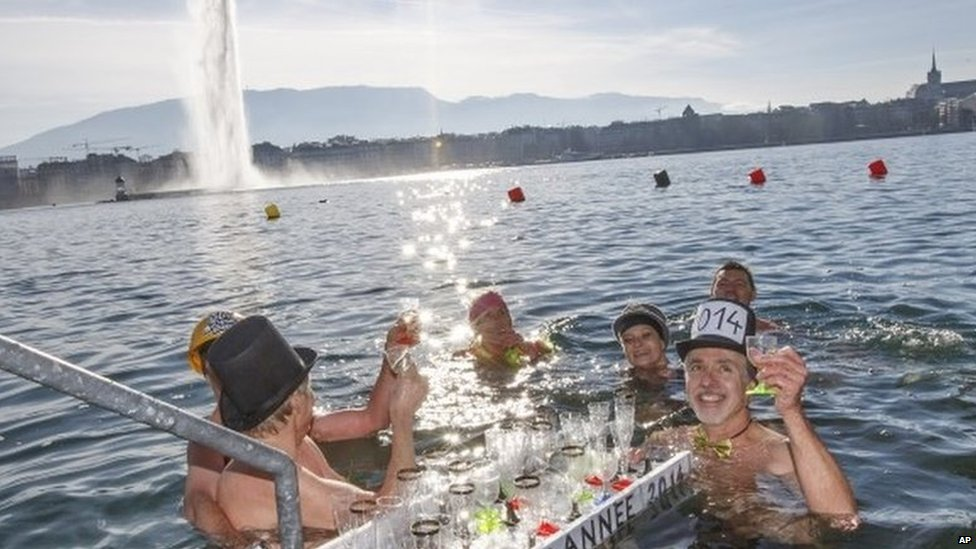 People toast with champagne while swimming in the cold water, during the annual swim in Lake Geneva
