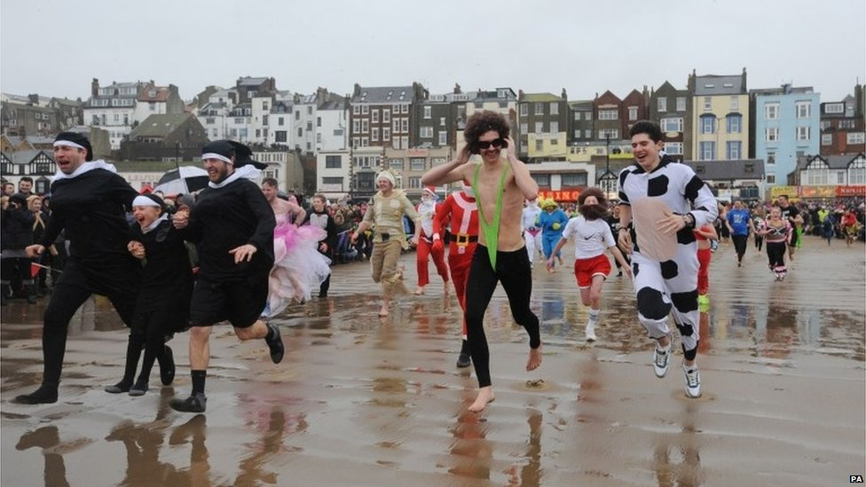 Competitors run towards the sea for the annual New Year's Day Dip in the South Bay at Scarborough