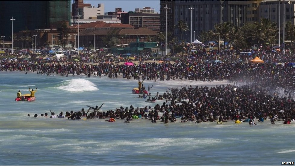 Lifeguards control the crowd as people visit the beach on New Year's Day in Durban, Jan 1st 2014.