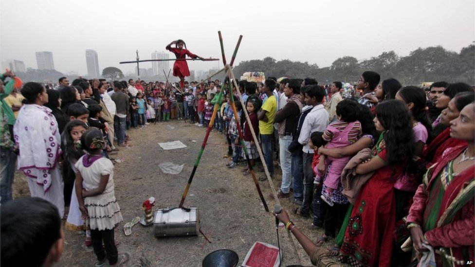 Indian people watch as a girl performs a rope balancing act at a park in Calcutta, India, 1 January 2014.