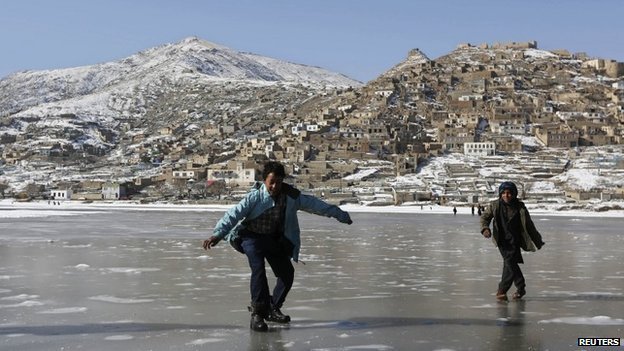 Afghan children play on a frozen lake in Kabul, December 31, 2013. REUTERS/Omar Sobhani