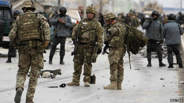NATO troops and Afghan policemen inspect at the site of a bomb attack in Kabul December 27, 2013