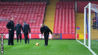 Referee Mike Dean checks the condition of the pitch before Crystal Palace host Norwich
