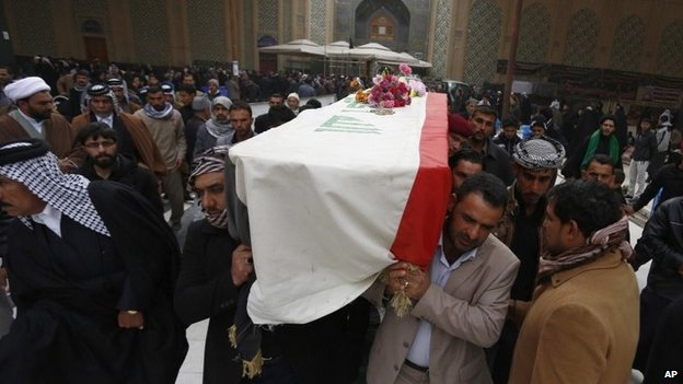 Mourners in the Shia holy city of Najaf hold the coffin of a soldier killed in the city of Ramadi (30 December 2013)