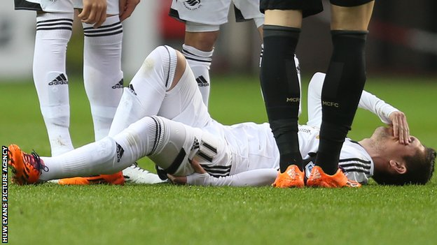Swansea City's Pablo Hernandez holds his hamstring