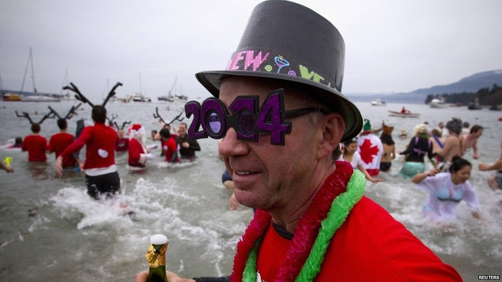 Participants run into English Bay during the 94th annual New Year's Day Polar Bear Swim in Vancouver, Canada Jan 1, 2014