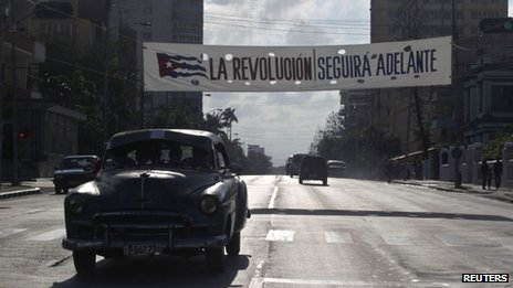 "A car drives past under a banner that reads ""The Revolution will continue forward"" in Havana on 31 December, 2013"