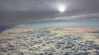 A view from a plane of clouds, blue sky and grey blanket cloud. The sun is trying to shine through the cloud.