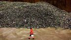 A worker at a glass recycling centre walks past a pile of glass bottles on 2 January 2014 in Gameren, The Netherlands
