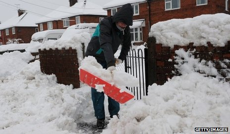 A woman clears snow outside her north Wales home in March
