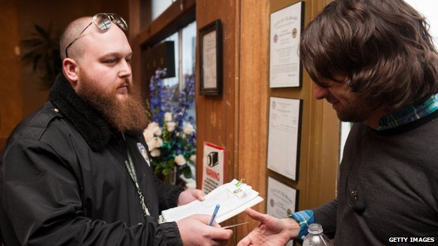 Head of security Kurt Britz (L) checks the driver's licence of Adam Hartle of Jacksonville, Florida at the 3-D Denver Discrete Dispensary 1 January 2014
