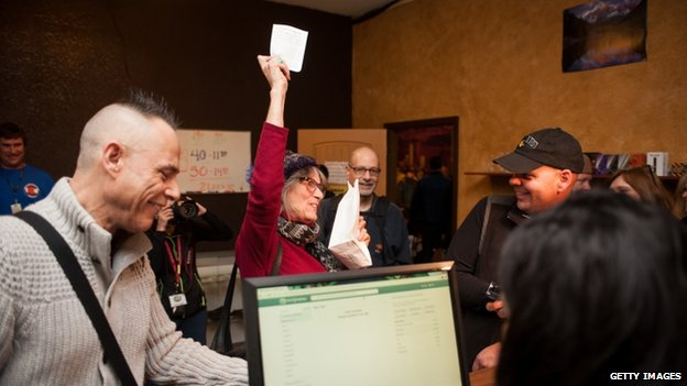 Lynne Johnston of Los Angeles, California celebrates after purchasing marijuana products at the 3-D Denver Discrete Dispensary 1 January 2014