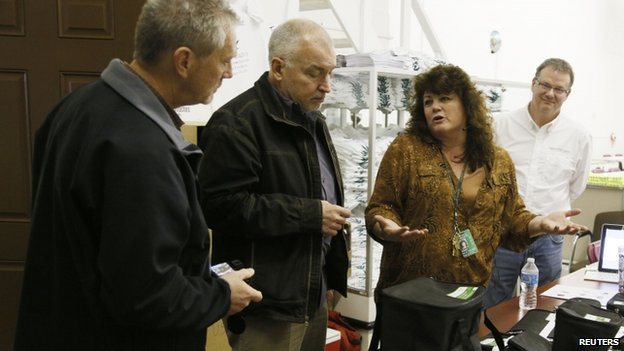 Cheri Hackett, (2nd right) co-owner of the Botana Care marijuana store talks to Colorado Marijuana Enforcement officials (L) just before opening her doors to customers for the first time in Northglenn, Colorado 1 January 2014