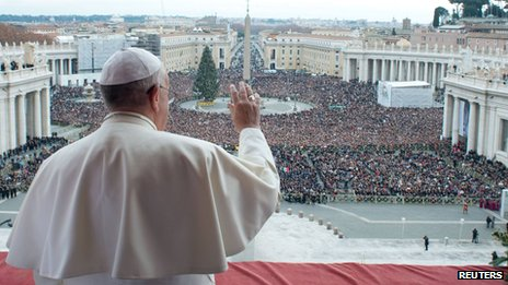 "Pope Francis waves as he delivers his first ""Urbi et Orbi"" message from the balcony overlooking St Peter's Square at the Vatican (25 Dec 2013)"
