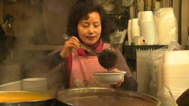 A lady serves red bean porridge in Seoul's Kwangjang Market