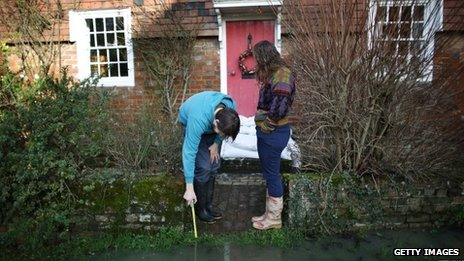 A man uses a stick to test the depth of water outside a house