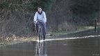 A man rides a bicycle through flood water