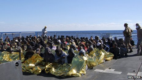 Migrants sit in an Italian navy vessel off the coast of Sicily (2 January 2014)