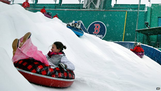 "Tubers slide down the ""Monster Sled"" adjacent to the left field wall as snow falls at Fenway Park in Boston, 2 January 2014"