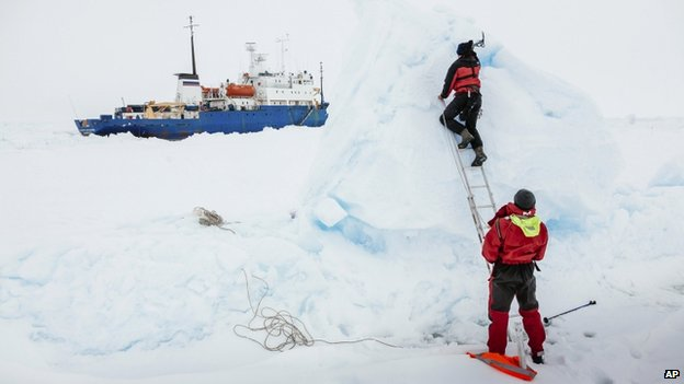 Ben Maddison and Ben Fisk from the Russian ship MV Akademik Shokalskiy work to place a wind indicator atop an ice feature near the trapped ship 1,500 nautical miles south of Hobart, Australia, 31 December 2013