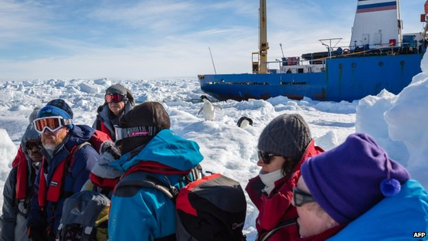 The first load of passengers from the stranded Russian ship MV Akademik Shokalskiy wait for a helicopter from the nearby Chinese icebreaker Xue Long to pick them up, 2 January 2014