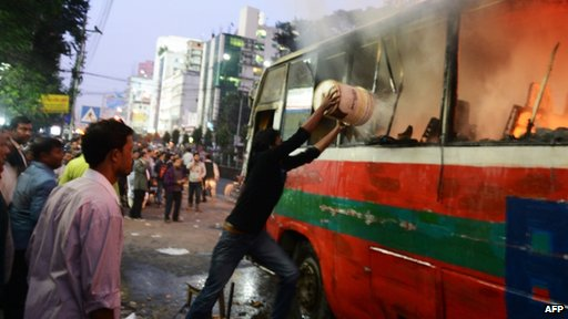 A Bangladeshi resident throws water onto a burning bus in Dhaka on 2 January 2014.
