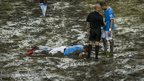 Referee Anthony Taylor and Manchester City's Javi Garcia stand over striker Alvaro Negredo lying inured in the mud during the Asia Trophy final against Sunderland. City won the match 1-0 at Hong Kong Stadium.