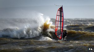 A windsurfer enjoys the stormy conditions in the sea off of Mudeford beach in Dorset