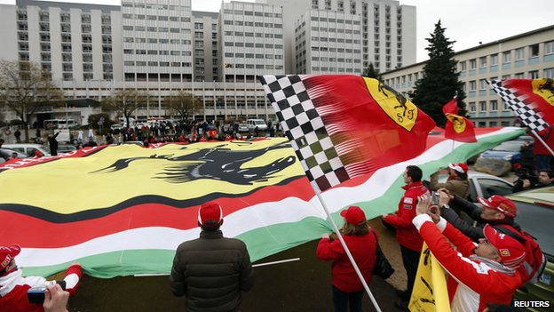 Ferrari fans from France, Italy and Germany display a giant Ferrari flag as they attend a silent 45th birthday tribute to seven-times former Formula One world champion Michael Schumacher (3 Jan 2014)