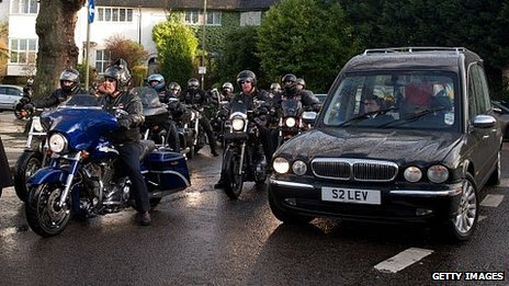 Members of the Hell's Angels motorcycle club form a guard of honour around the hearse