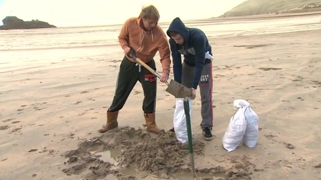 People fill sandbags on the beach at Perranporth in Cornwall