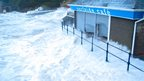 Sea waves rise up over stairs and railings, hitting a seaside cafe.