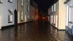 A flooded residential street at night.