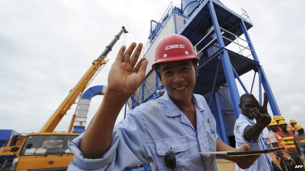A Chinese employee of the China Machinery Engineering Corporation poses in front of a tar factory on the construction site of a highway between Abidjan and Bassam in September 2013 in Bassam