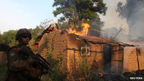 French soldier next to a house on fire at a village in Bossangoa, north of Bangui (3 January 2014)