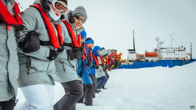 Passengers from the Russian ship MV Akademik Shokalskiy link arms and stamp out a helicopter landing site on the ice