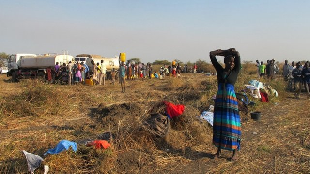 Displaced South Sudanese people filling cans with water from a UN tanker